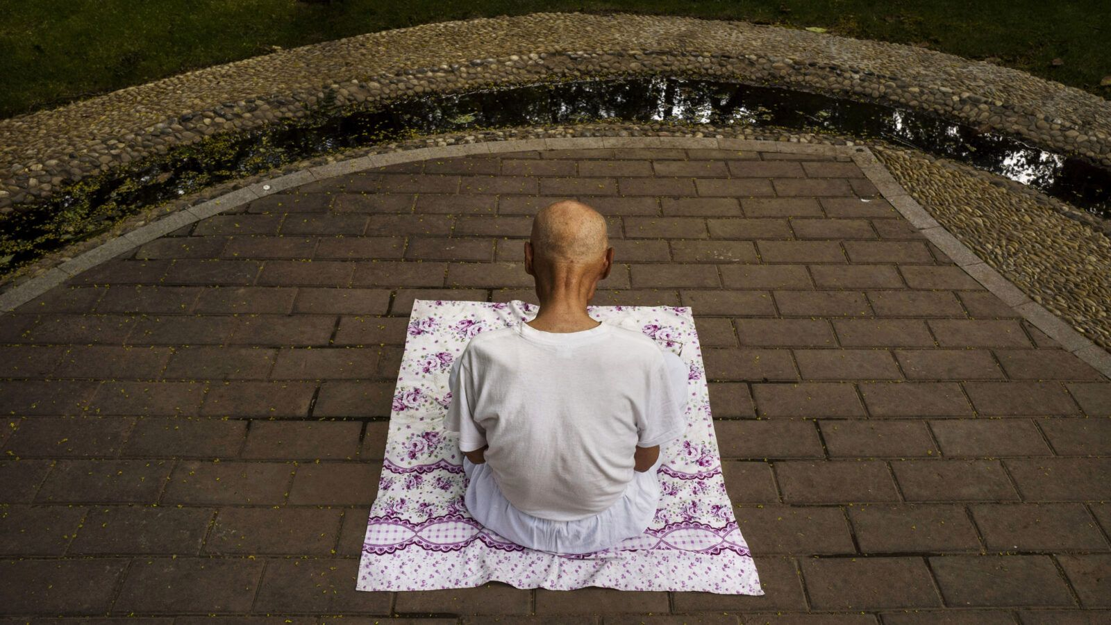 A man sitting on a blanket outside meditating